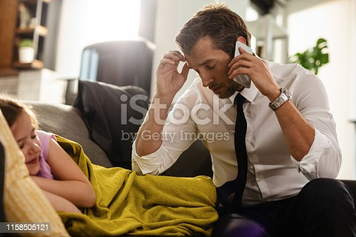 Worried business father talking on mobile phone while his daughter is sleeping on the sofa at home.
