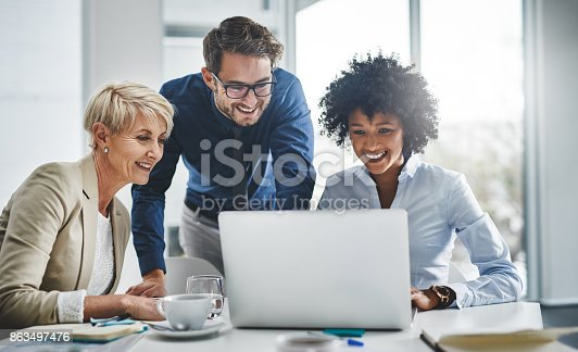 Shot of a group of businesspeople working together on a laptop