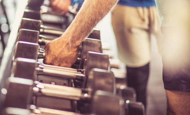 It's in shape despite its age. It's in shape despite its age. Senior man at gym taking weight. Focus is on hand. Close up. despite stock pictures, royalty-free photos & images