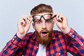 istock It's incredible! Close up portrait of young bearded man touching the spectacles and keeping his mouth open against gray background 939062522