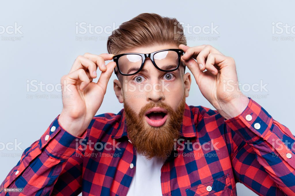 It's incredible! Close up portrait of young bearded man touching the spectacles and keeping his mouth open against gray background stock photo