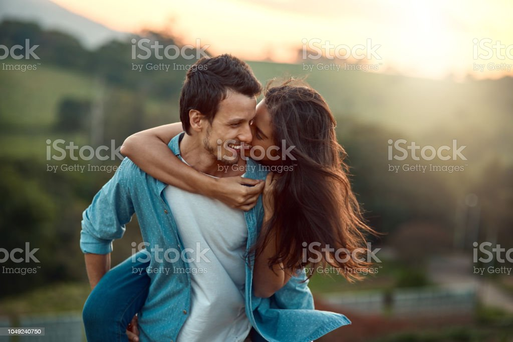 It's just you and me, babe Cropped shot of a handsome young man piggybacking his girlfriend while spending some time outdoors 20-29 Years Stock Photo