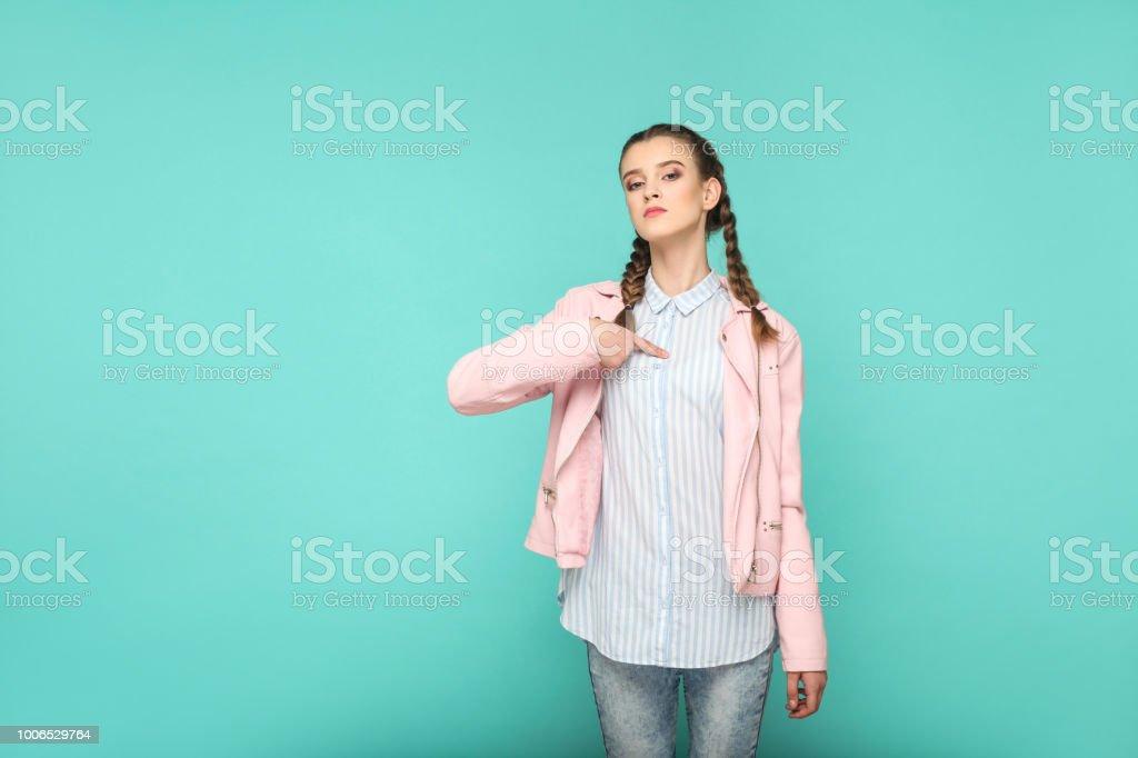 Die mich! stolz auf Portrait schöne süße Mädchen stehend mit Make-up und braunen Zopf Frisur in gestreiften hellblaues Hemd rosa Jacke. – Foto