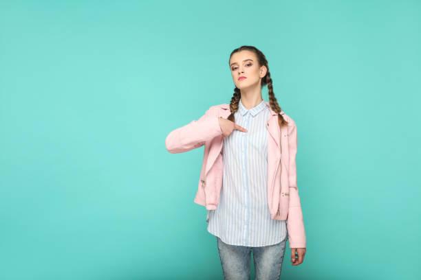 Its me! proud portrait of beautiful cute girl standing with makeup and brown pigtail hairstyle in striped light blue shirt pink jacket. Its me! proud portrait of beautiful cute girl standing with makeup and brown pigtail hairstyle in striped light blue shirt pink jacket. indoor, studio shot isolated on blue or green background. arrogant stock pictures, royalty-free photos & images