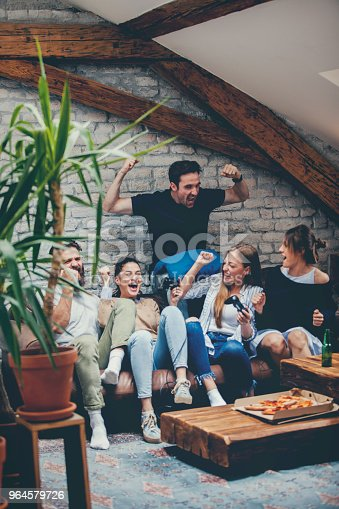 Group of friends are gathered at their friends apartment to enjoy and play some video games together. Two girls are playing some fighter game, and they are very passionate about winning that they are hitting joystick too fast. Behind and by their side are two guys and one girl, who are divided and each one is cheering for their favorite. In one moment attractive brunette  wins the fight and celebrate with guy right next to him, while other two friends are comforting girl who lost match.