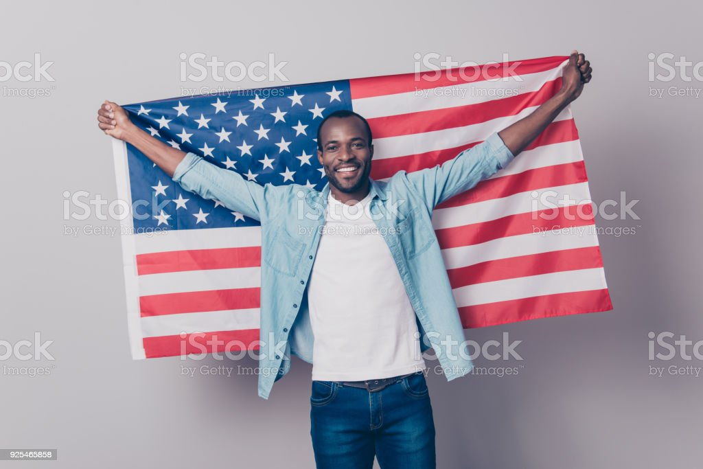 It's my native country! Portrait of cheerful glad excited confident with toothy beaming smile student wearing denim casual outfit holding flag of the USA isolated on gray background stock photo