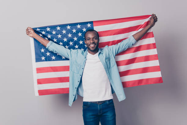 It's my native country! Portrait of cheerful glad excited confident with toothy beaming smile student wearing denim casual outfit holding flag of the USA isolated on gray background It's my native country! Portrait of cheerful glad excited confident with toothy beaming smile student wearing denim casual outfit holding flag of the USA isolated on gray background citizenship stock pictures, royalty-free photos & images