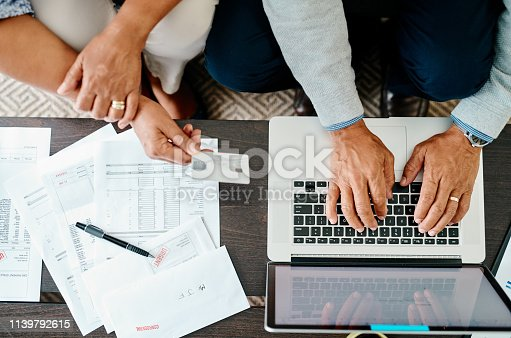 High angle shot of a couple using a laptop and credit card while sorting their finances together at home