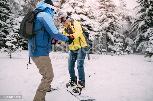Photo of a senior couple helping each other with snowboarding lessons