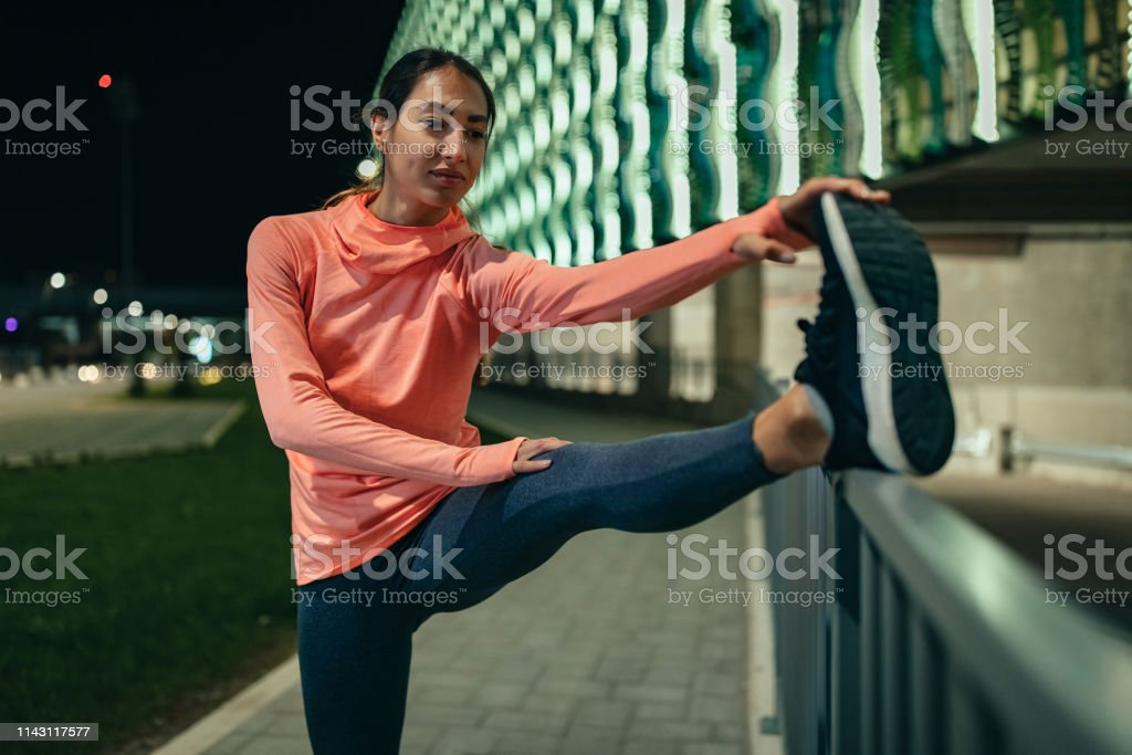 Sporty young woman working out on the city streets
