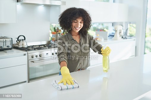 Shot of a young woman cleaning a kitchen counter at home