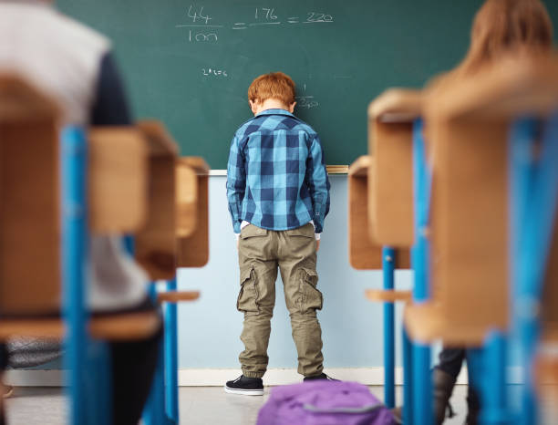 It's no fun feeling like a loser Rear view shot of an elementary school boy leaning with his head on the chalkboard in class learning difficulty stock pictures, royalty-free photos & images