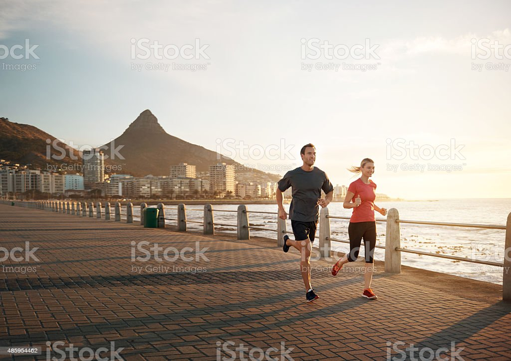 Shot of a young couple jogging together on the...