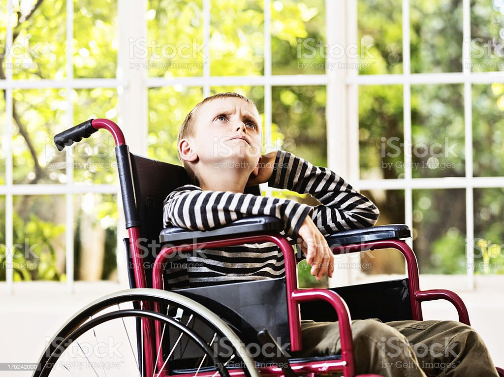 It's not fair! Angry boy in wheelchair resents his situation stock photo