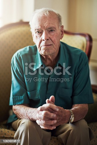 Cropped portrait of a senior man sitting by himself in a living room