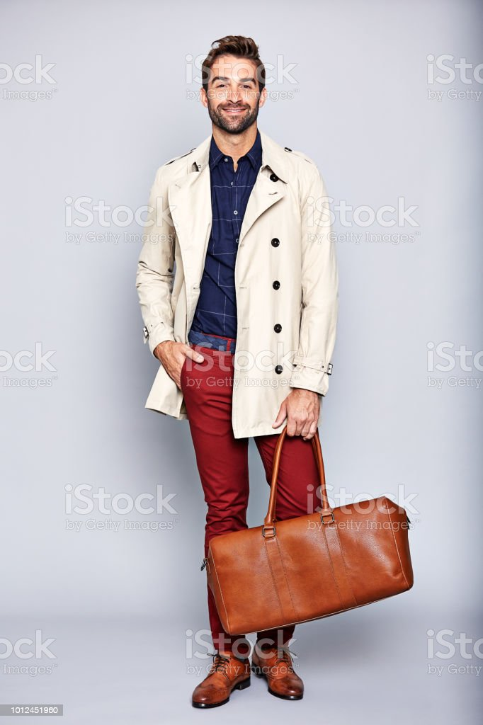Studio portrait of a handsome young man carrying a suitcase against a...
