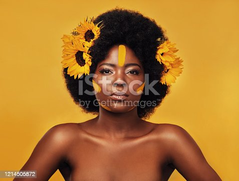 Studio portrait of a beautiful young woman posing topless with sunflowers in her hair against a mustard background
