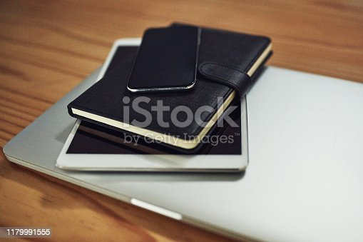 Still life shot of digital devices and a diary on a table in an office