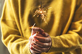 It's party time! Unrecognizable woman holding a sparkly sparkler in her hands