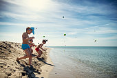 Summer Easter on beach. Kids are running and catching Easter eggs.\nNikon D850