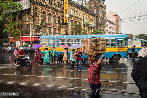 Kolkata,India- June 1, 2014: This is a typical monsoon afternoon in Kolkata.It's still raining in so in the picture people are crossing the streets with umbrelas.  Shot near Esplande street in Kolkata.