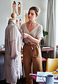 Shot of a young fashion designer working on a garment hanging over a mannequin