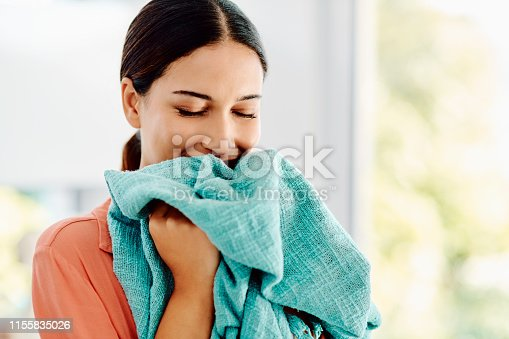 Cropped shot off a young woman smelling a freshly washed towel at home