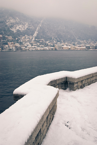 It's snowing on Lake Como. The city in the photo is Como.