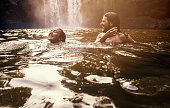 Shot of a young couple swimming together in a lake