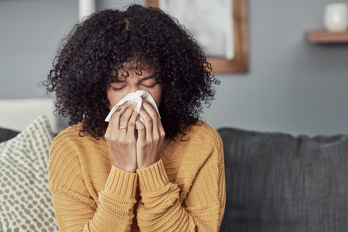 Shot of a young woman blowing her nose with a tissue at home