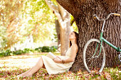 A pensive woman sitting against a tree with a book