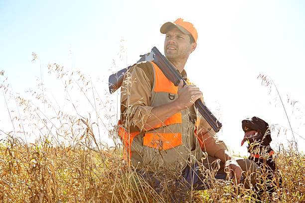 It's so quiet out here! A man out hunting with his retriever dog beside him bird hunting stock pictures, royalty-free photos & images