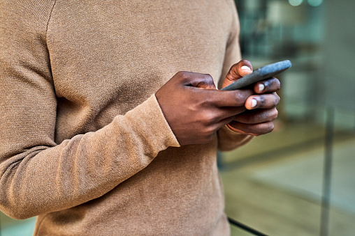 Closeup shot of an unrecognisable businessman using a cellphone in an office