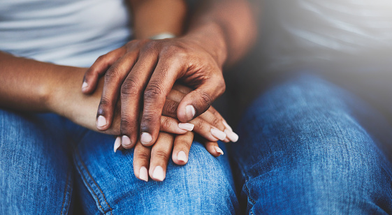 Closeup shot of an unrecognizable couple holding hands in comfort