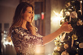 Smiling caucasian woman at home. Decorating Christmas tree. Wearing sparkly dress. Evening or night.