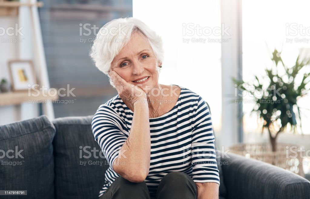 Portrait of a happy senior woman relaxing on the sofa at home