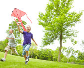 A happy young boy flying a kite outside in a park