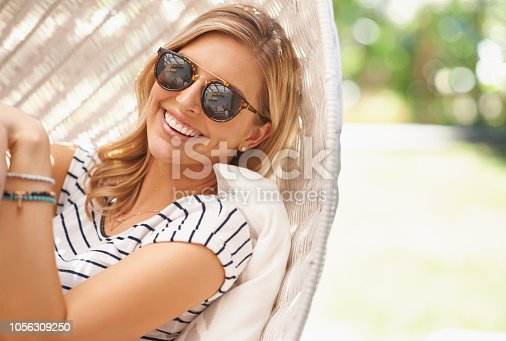 Cropped portrait of an attractive and happy woman relaxing outdoors in her backyard