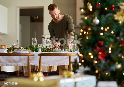 Shot of a young man setting a table for a Christmas party at home