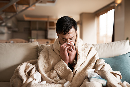 Cropped shot of a young man suffering with flu while sitting wrapped in a blanket on the sofa at home