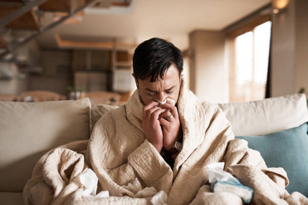 It's the season of sneezes Cropped shot of a young man suffering with flu while sitting wrapped in a blanket on the sofa at home flu stock pictures, royalty-free photos & images