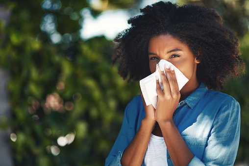 Portrait of a young woman blowing her nose with a tissue outside