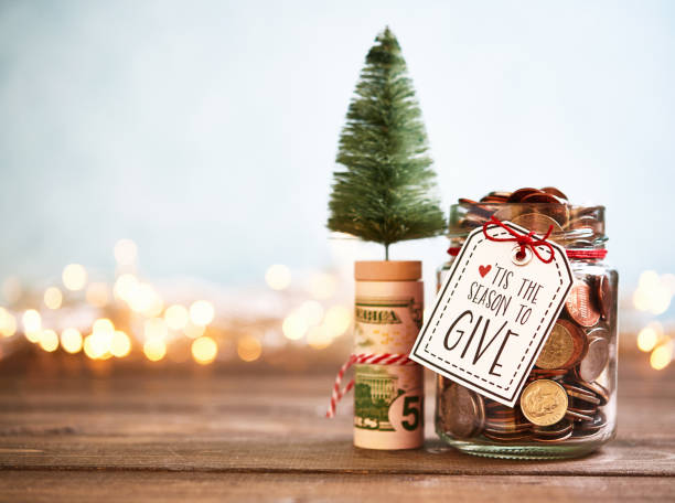 it's the season to give. donation jar with money - gift tag note stock photos and pictures