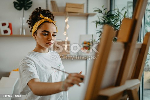 Photo of young females artist in her apartment
