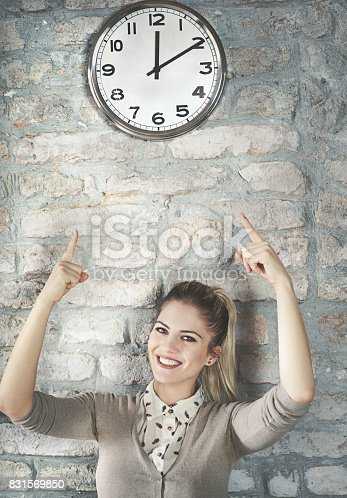 Closeup front view of smiling mid 20's woman standing against a brick wall and pointing to a big clock above her head.