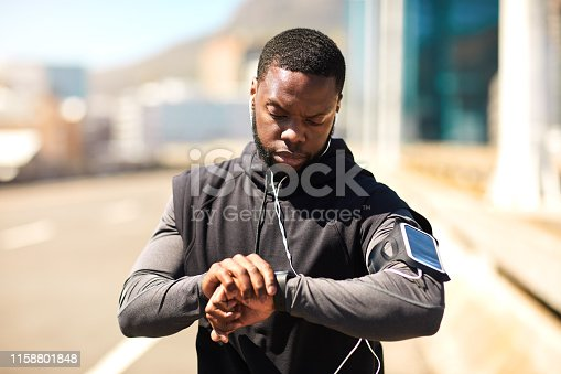 Shot of a sporty young man looking at his wristwatch while out exercising