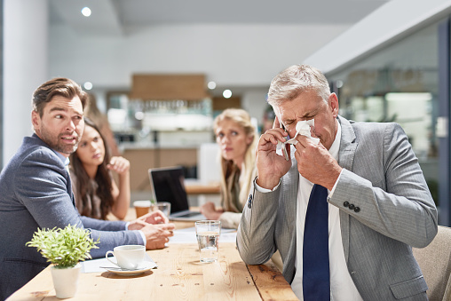 Cropped shot of a businessman blowing his nose while his colleagues look on in disgust