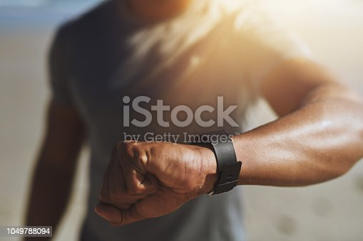 Closeup shot of an unrecognizable man checking his smartwatch while exercising outdoors