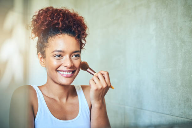 It's time to glow up! Shot of a young woman using a makeup brush while looking in her bathroom mirror blusher make up stock pictures, royalty-free photos & images