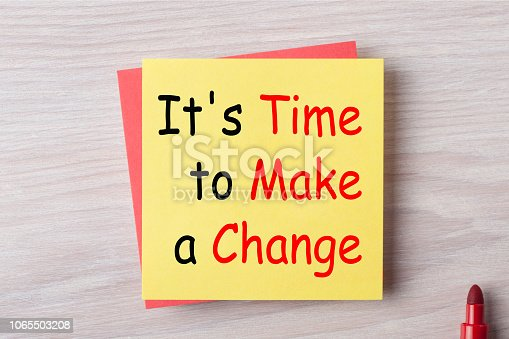 It's Time to make a change written on note with marker pen.